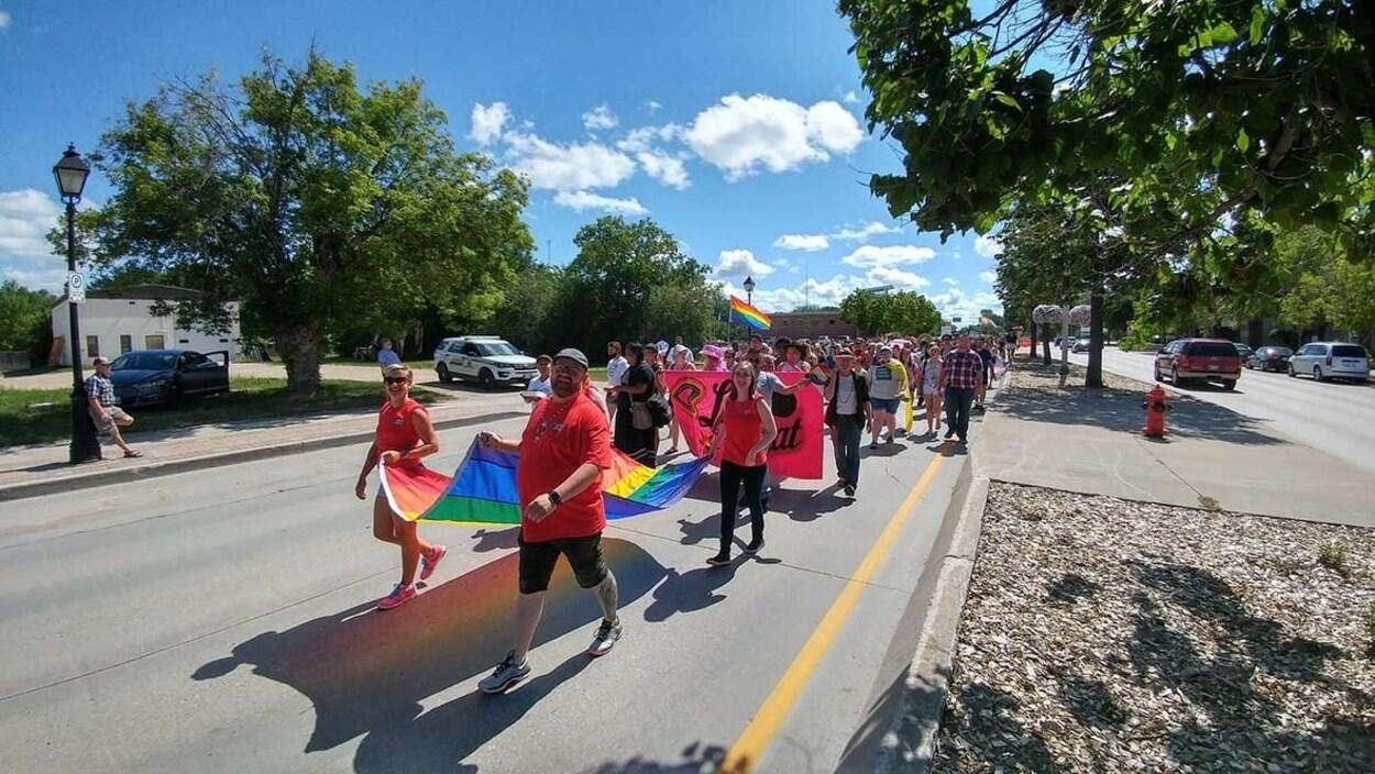 Des centaines de personnes marchent sous un ciel bleu au défilé de la fierté gaie à Steinbach