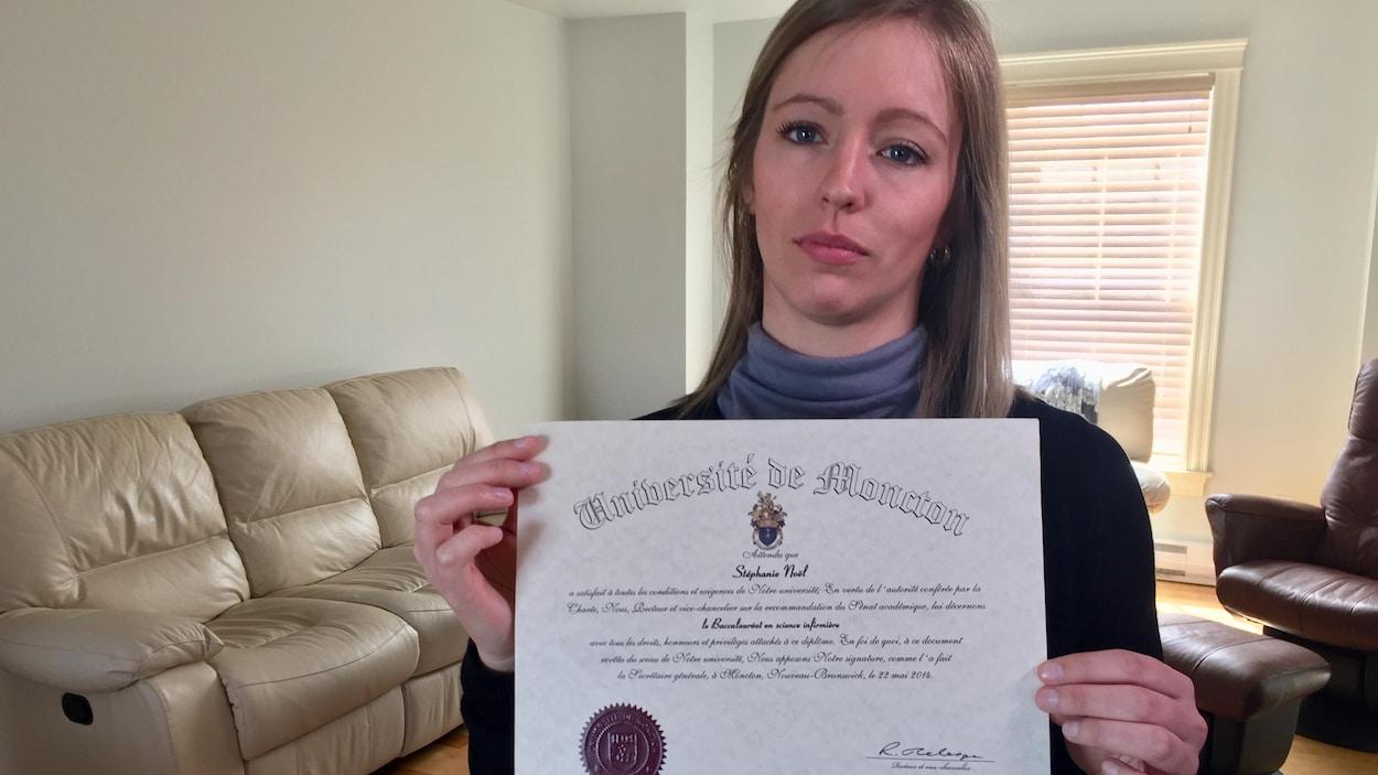 Une jeune femme triste qui tient son diplôme de sciences infirmières dans son salon.