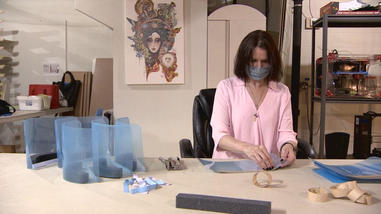 Une femme portant un masque assemble une visière.