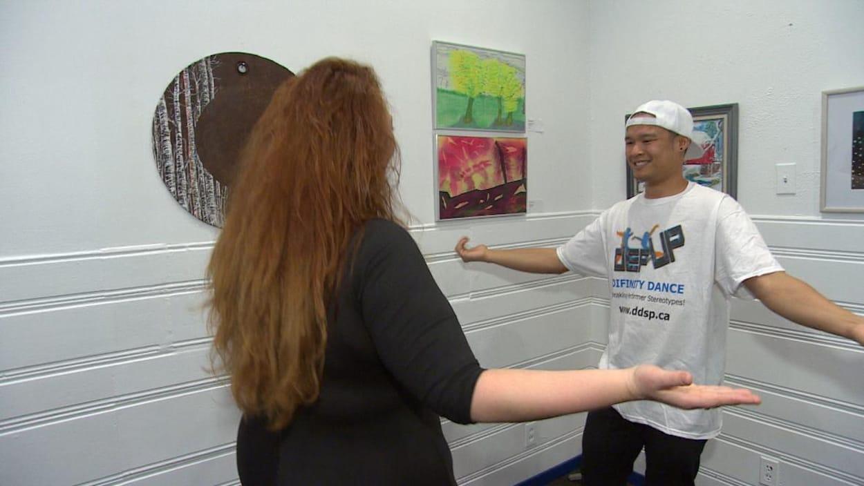 Stephanie Strugar (à gauche) et Jordan Sangalang (à droite) pratiquent des mouvements de danse dans une salle aux murs décorés de toiles peintes.