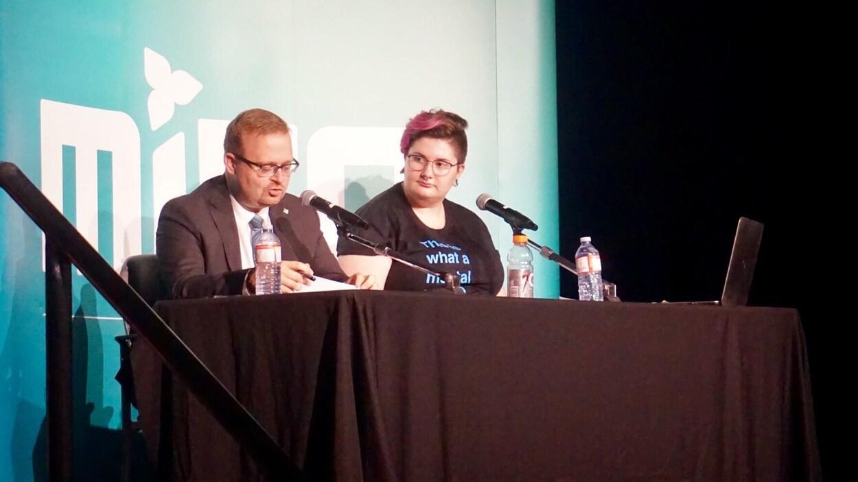 Un homme et une femme au podium devant une affiche du MIFO