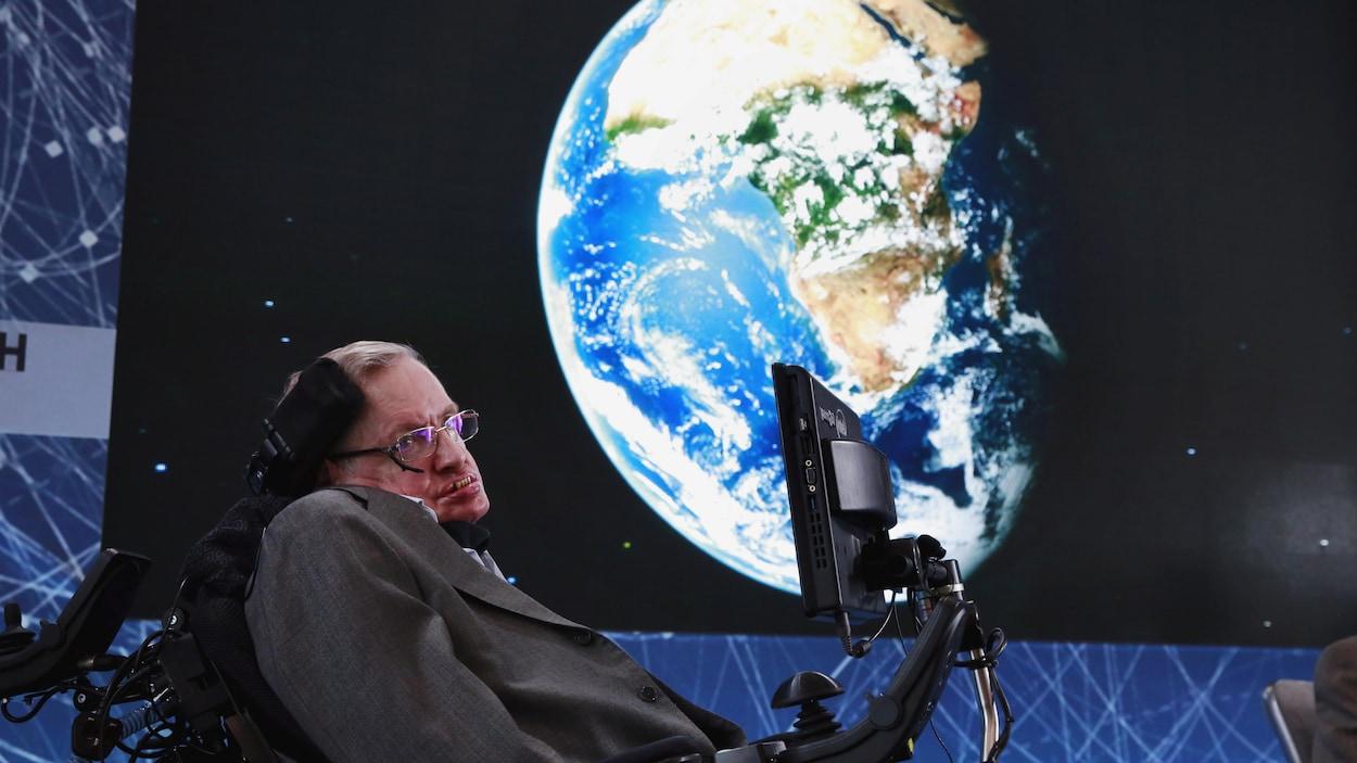 Stephen Hawking pose devant une image de la Terre.