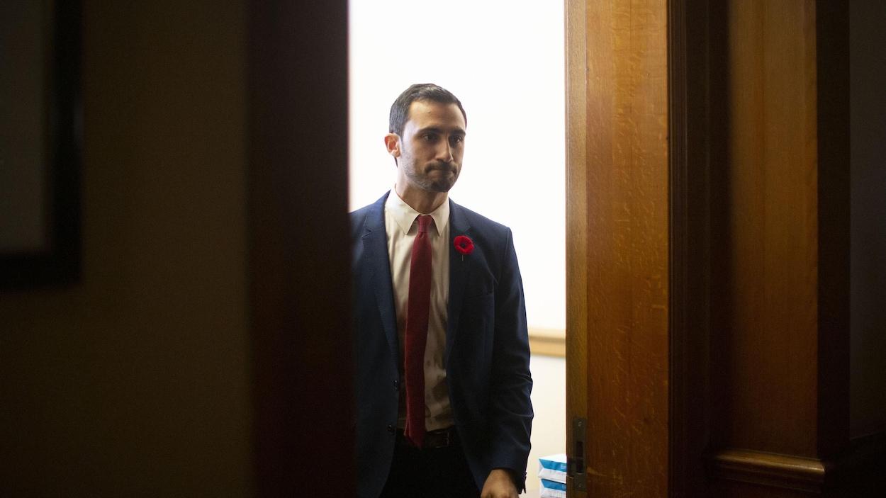 Le ministre de l'Éducation de l'Ontario, Stephen Lecce, sort d'un bureau en se pinçant les lèvres.