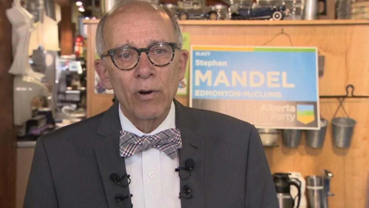 vue sur un homme aux cheveux gris et avec des lunettes. Il porte un veston avec un noeud papillon.