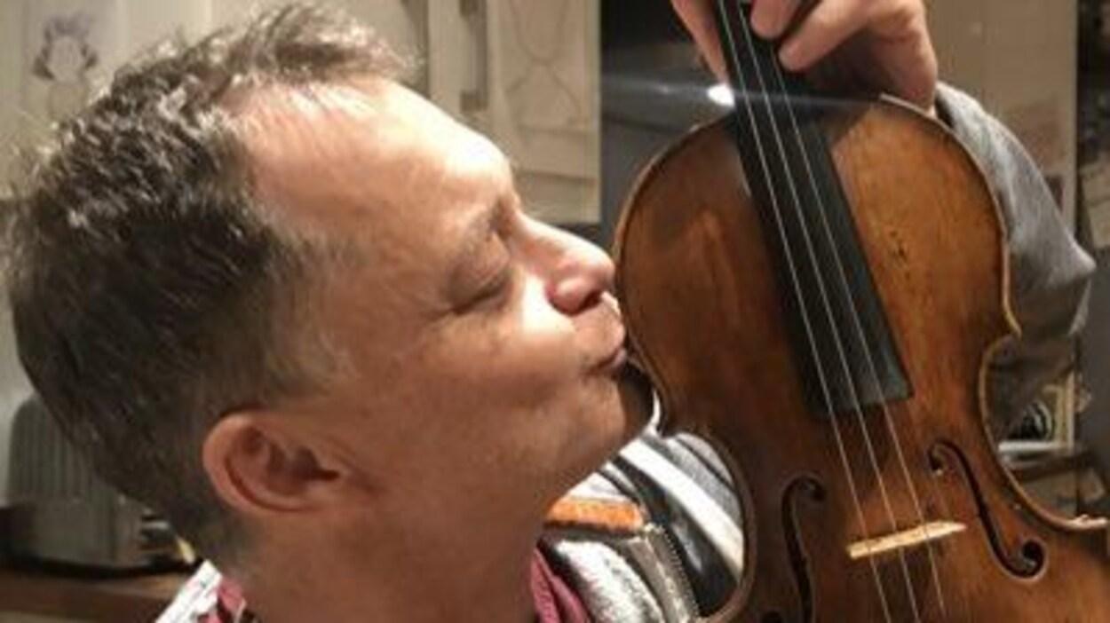 L'homme embrasse le violon.