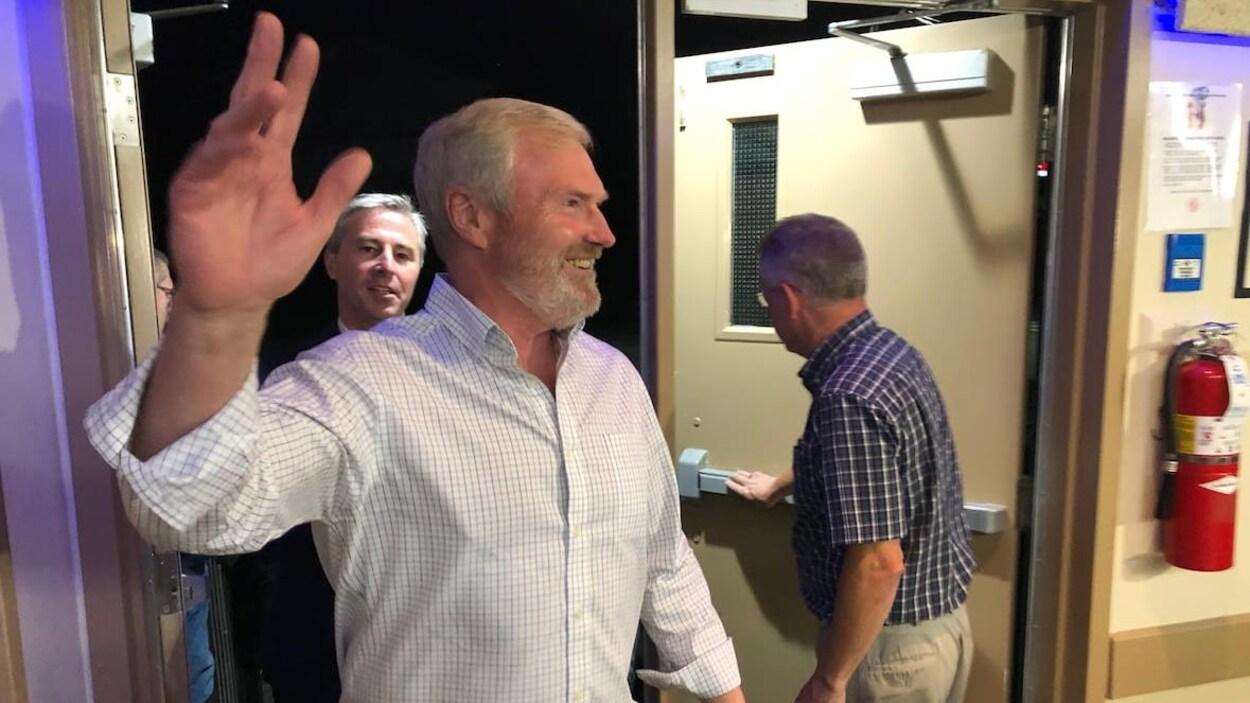 Steve Craig salue en entrant dans la salle.
