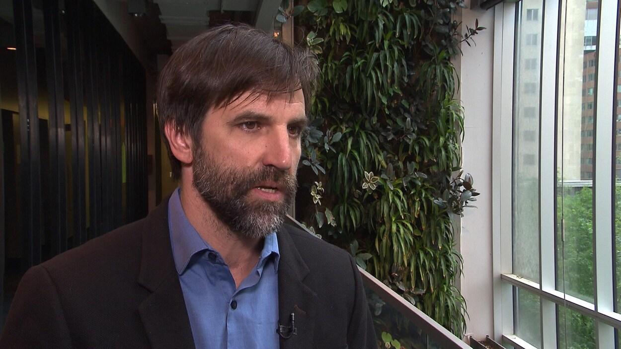 Steven Guilbeault en entrevue, devant des plantes.