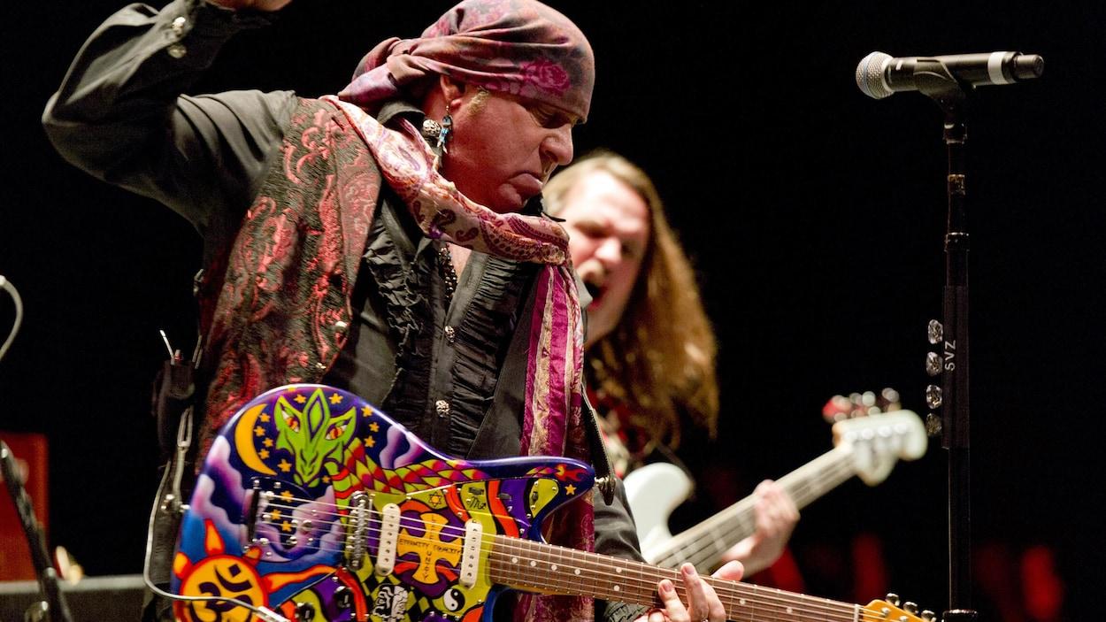 L'homme porte une écharpe sur la tête et joue de la guitare.