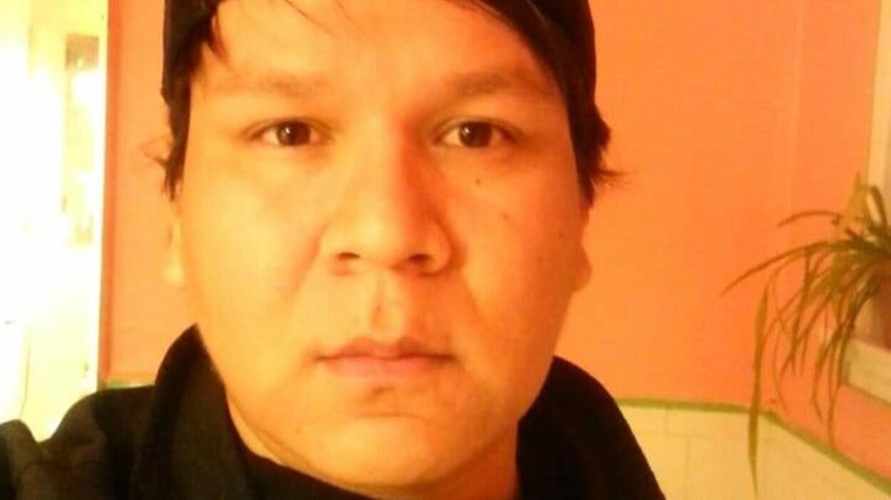 Un homme aux cheveux noirs et portant une casquette pose devant la caméra.