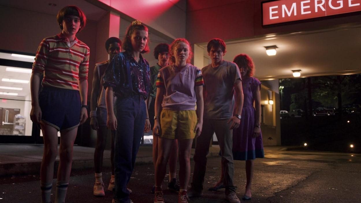 Un groupe de jeunes se trouve à l'extérieur des urgences d'un hôpital.