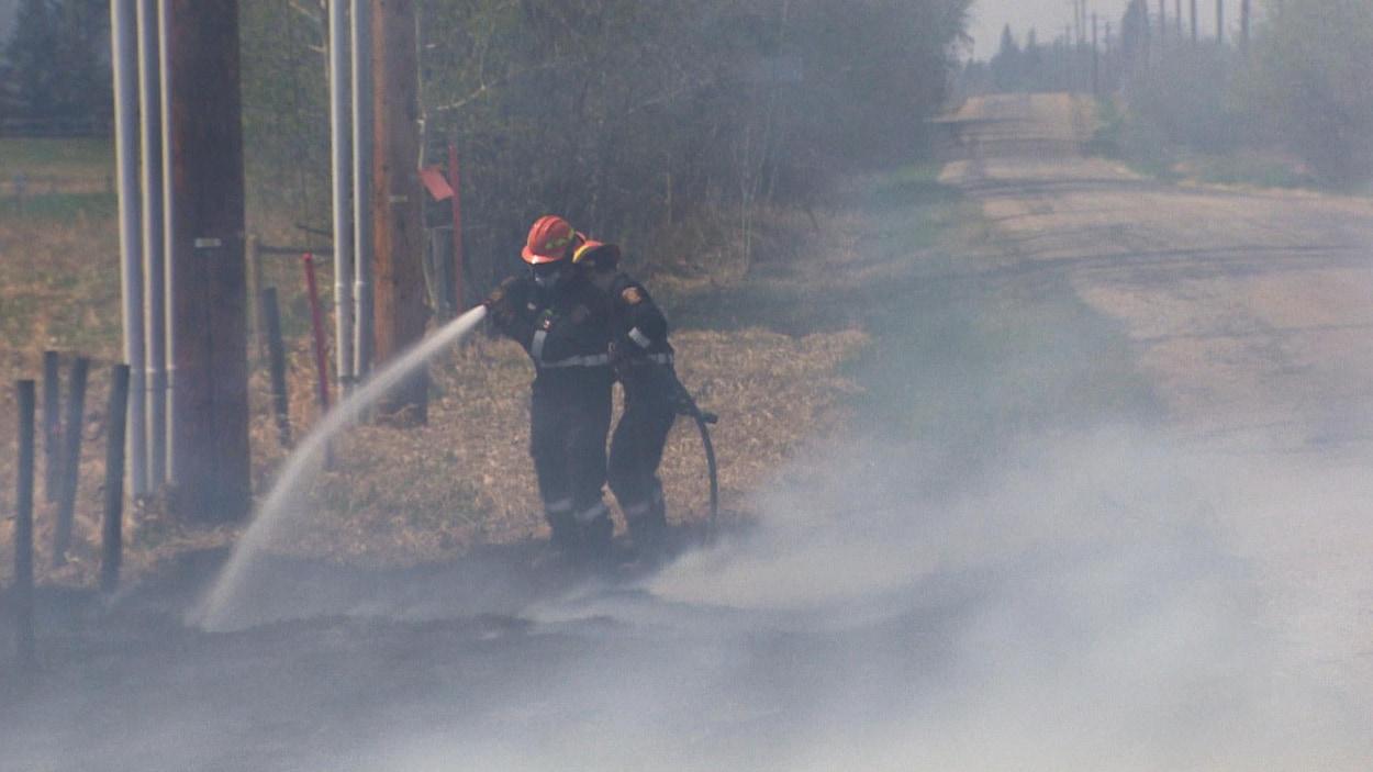 Des pompiers tiennent une lance d'incendie sur la route 564.