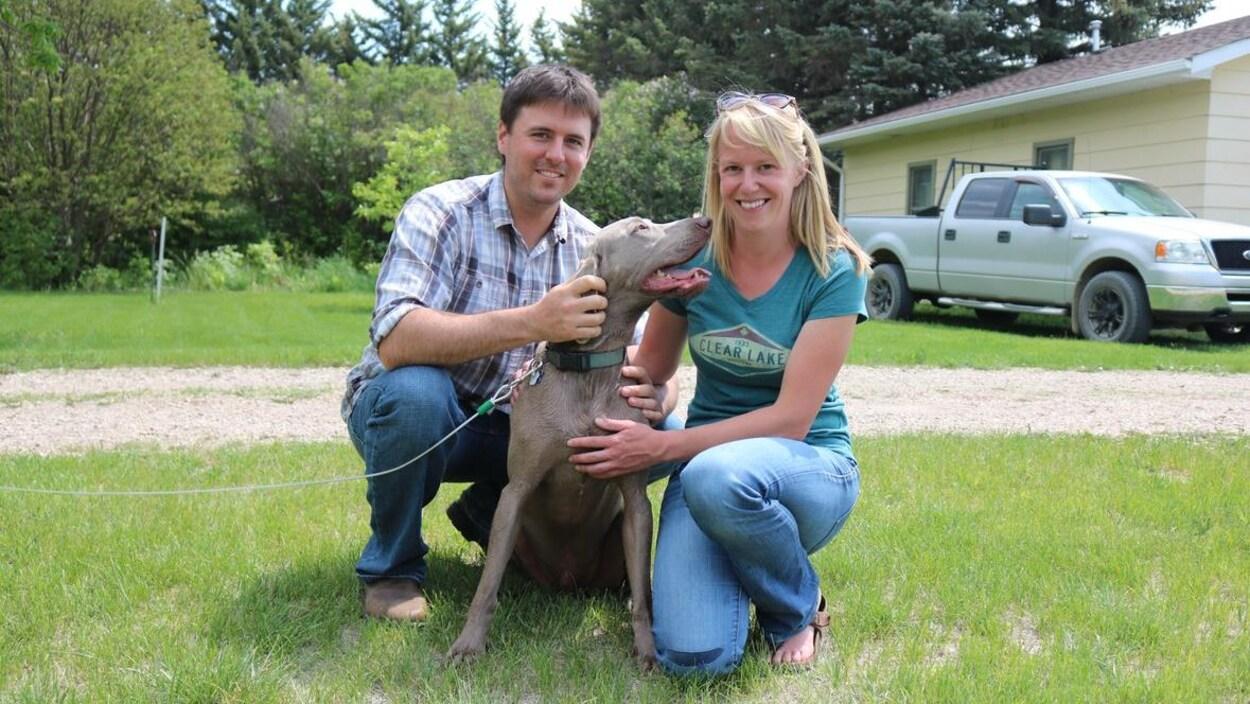 Kyle MacLintock et Erika Shuurmans sont agenouillés sur une pelouse avec leur chien Hercules attaché à une laisse.