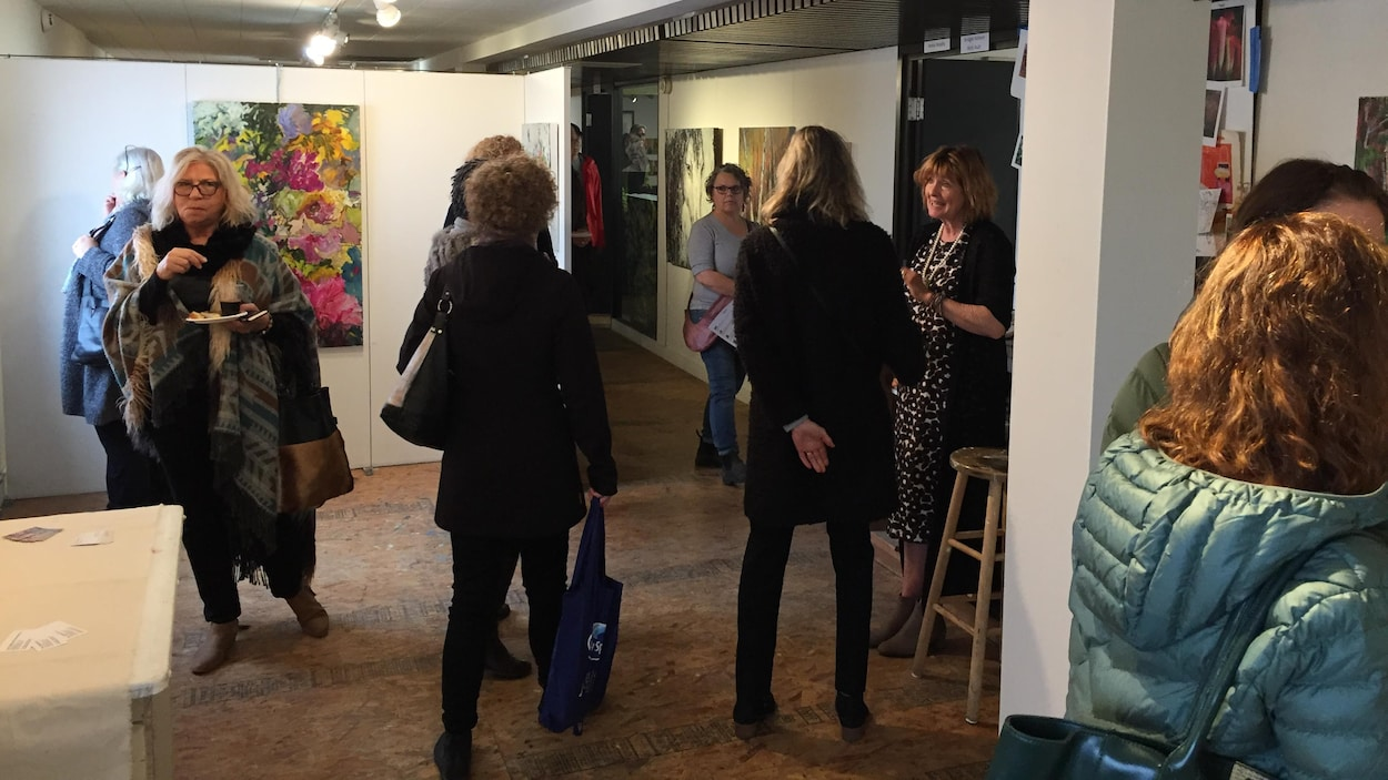 Des visiteurs déambulent dans les couloirs du Studio on 20th dont les tableaux sont accrochés aux murs.