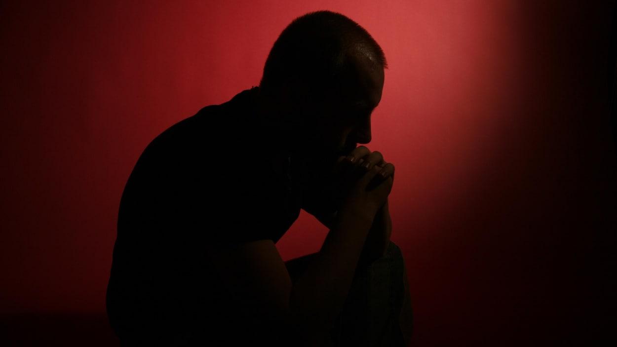 Un homme pensif devant un fond rouge et noir.