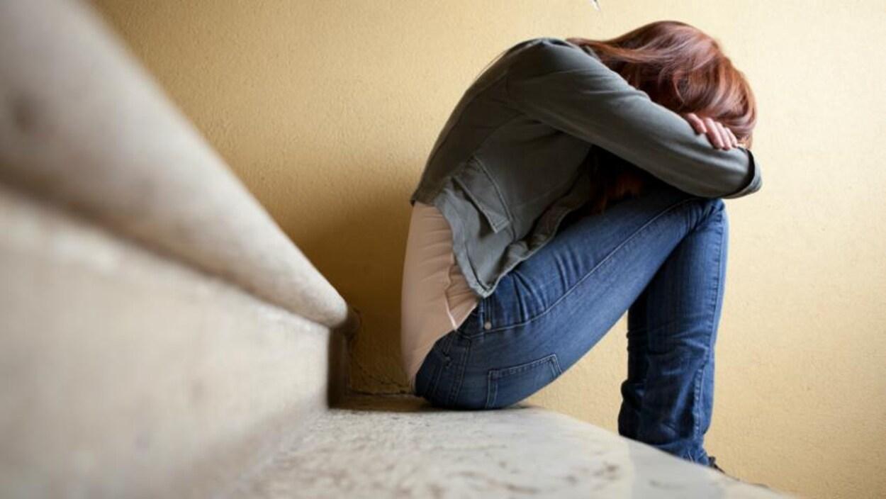 Une fille assise sur la marche d'un escalier, recroquevillée sur elle-même