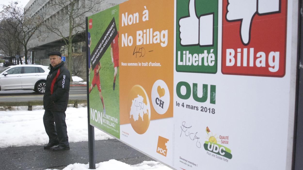 Un homme marche à côté d'une affiche sur le référendum en Suisse.