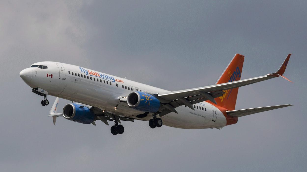 Un avion de Sunwing aux couleurs orange et bleue dans le ciel.