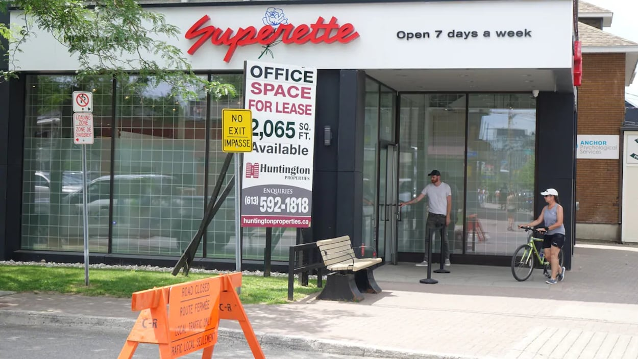 Deux personnes devant le magasin de cannabis Superette, situé dans le quartier Wellington Ouest d'Ottawa. Un panneau sur la rue indique que la rue est fermée et que seule la circulation locale y est permise.