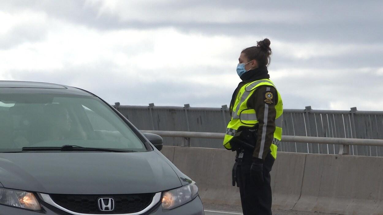 Une policière accostant une voiture.