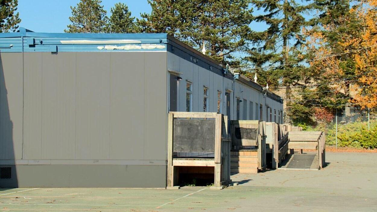 Des salles de classe mobiles alignées dans une cour d'école.