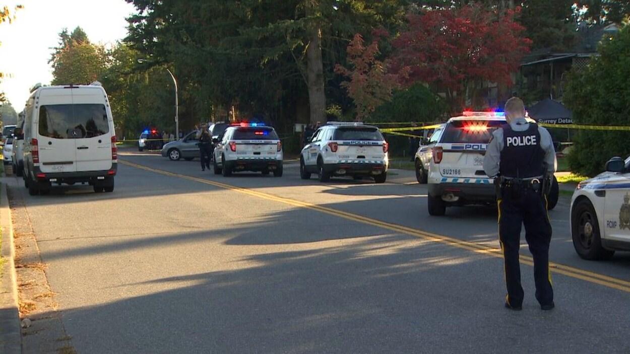 Des voitures de police et un policier de dos sont dans la rue.