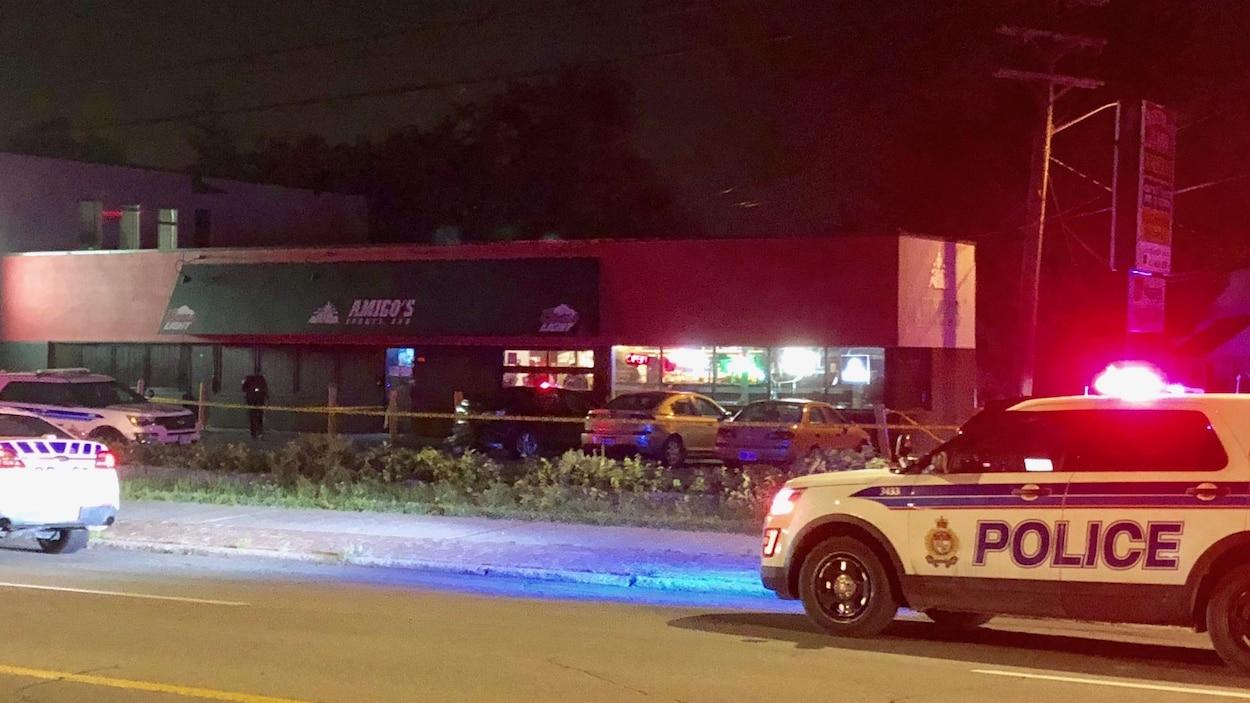 Deux voitures de police devant des commerces.