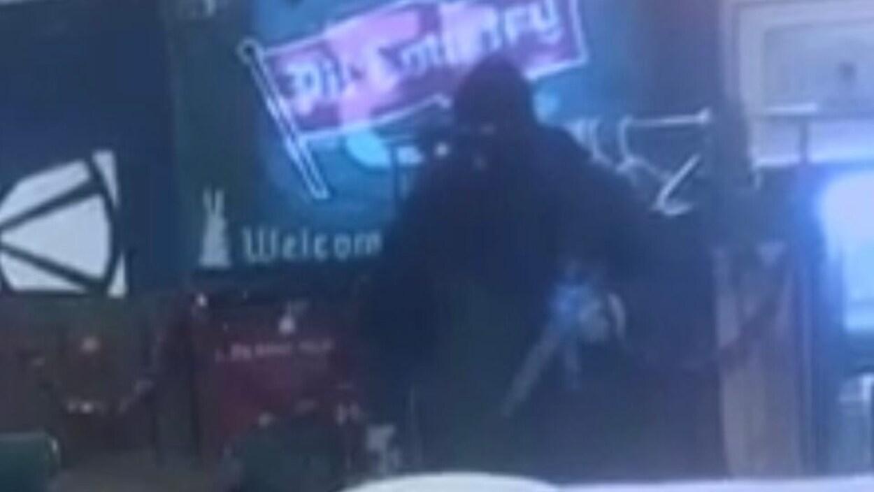 Image d'un homme masqué et armé.