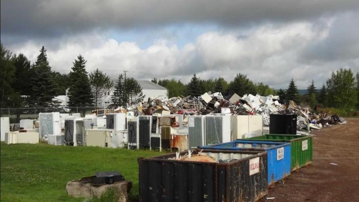 Des conteneurs et des appareils ménagers disposés devant un monticule de déchets sur un terrain clôturé.