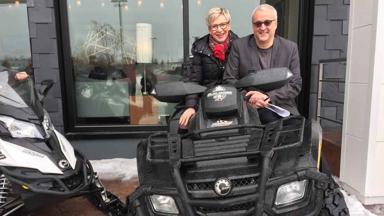 Suzanne Blais et Pierre Dufour sont assis sur un VTT, souriants.