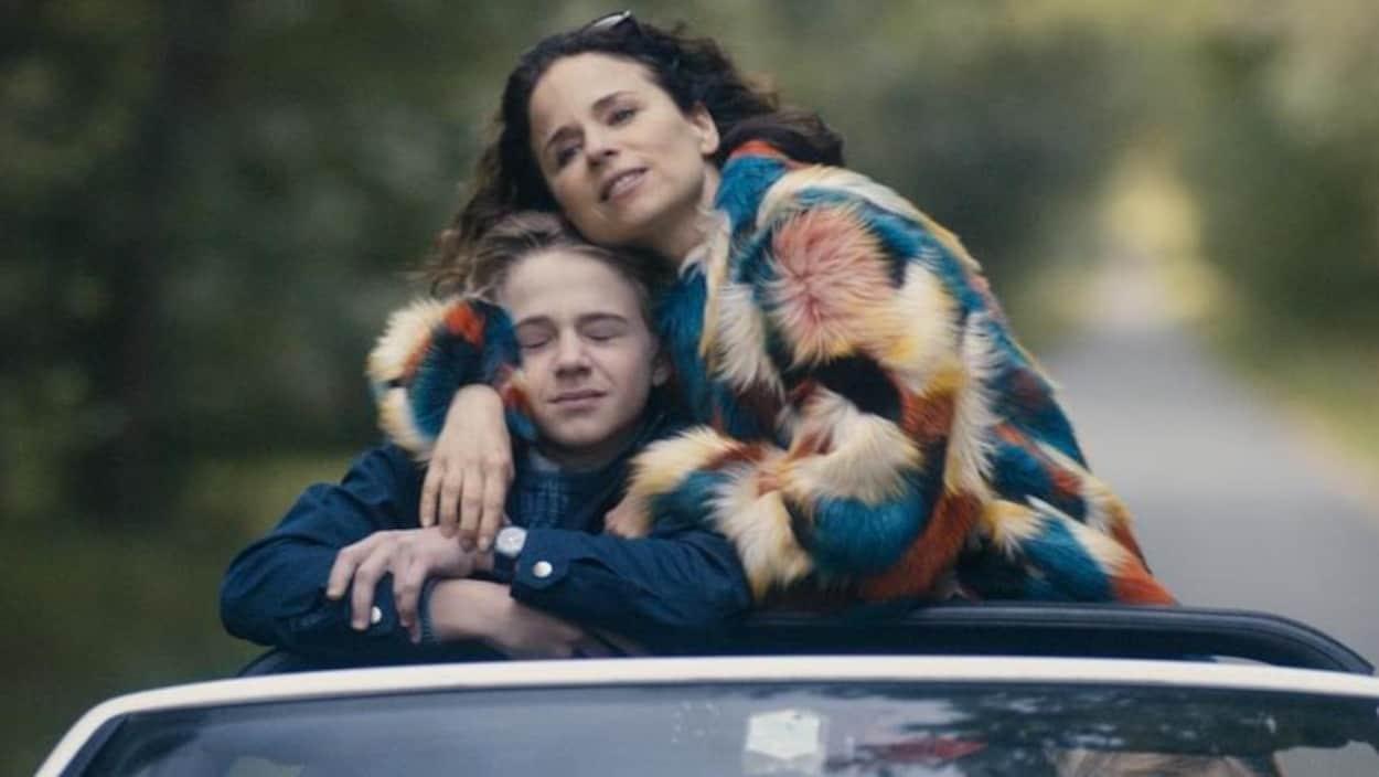 Une femme enlace un adolescent alors qu'ils sont debout dans une voiture.