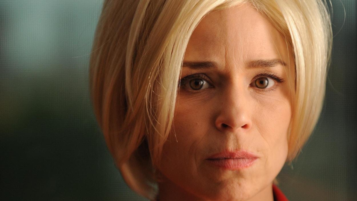 L'actrice porte une perruque blonde et regarde la caméra.