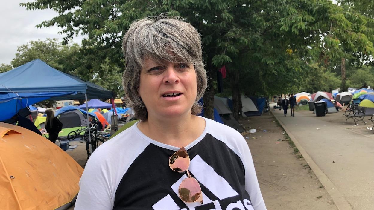 Un femme dans un parc où se trouve derrière elle des tentes.