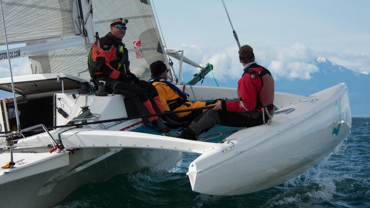 Trois matelots sont assis sur un catamaran en pleine navigation.
