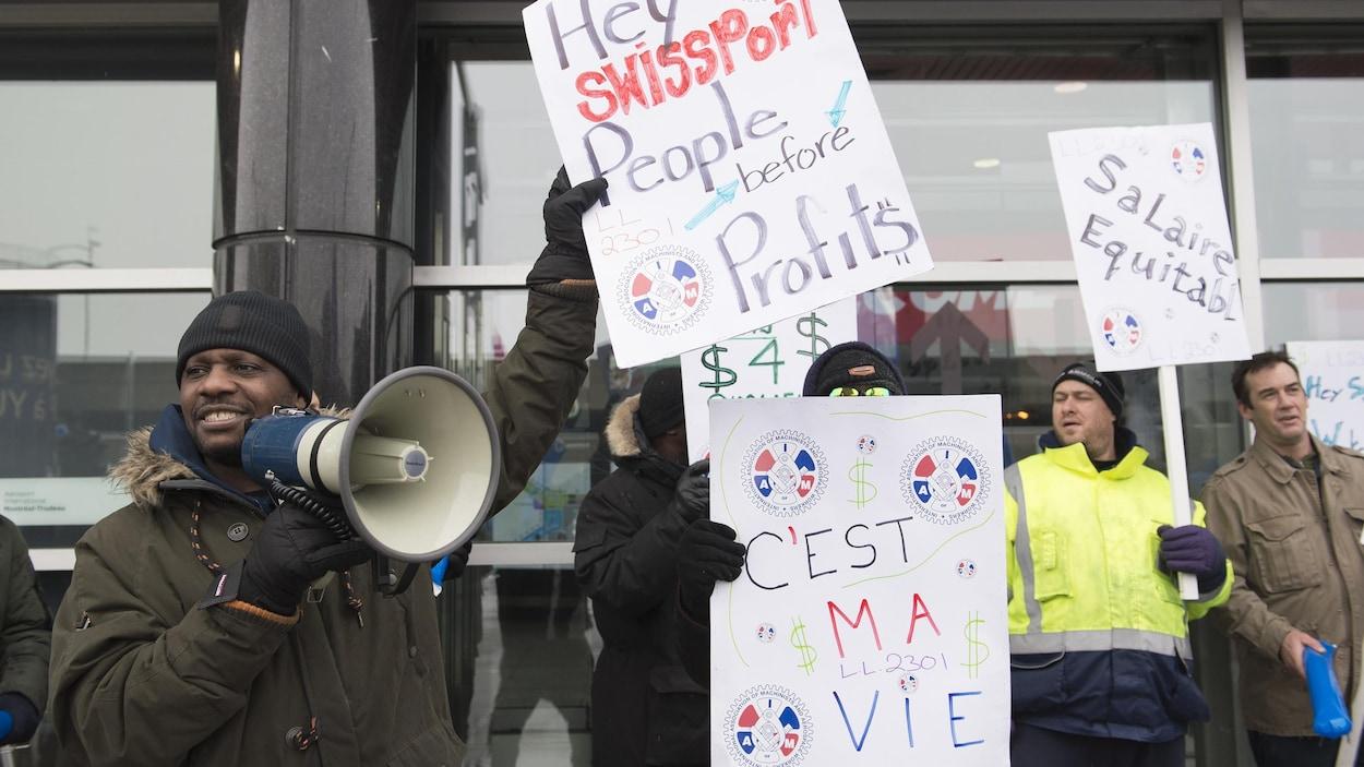 Des grévistes brandissent des pancartes.