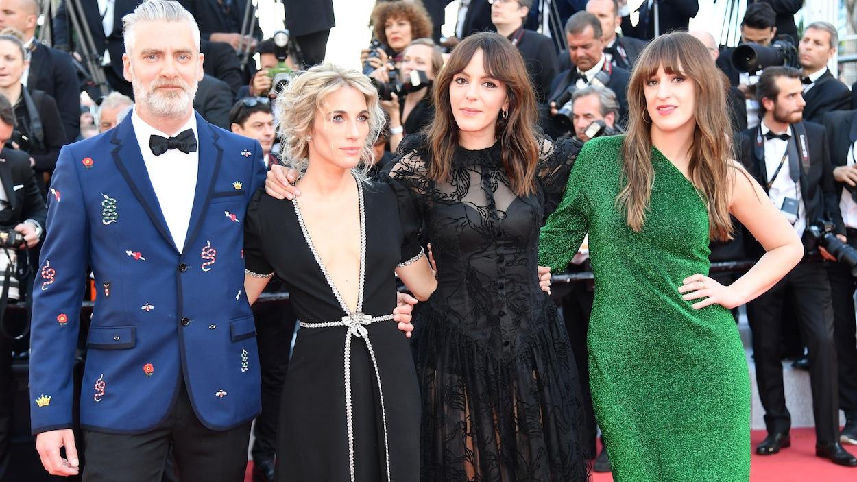 Les quatre personnes posent côte à côte en robes et costumes de soirée.