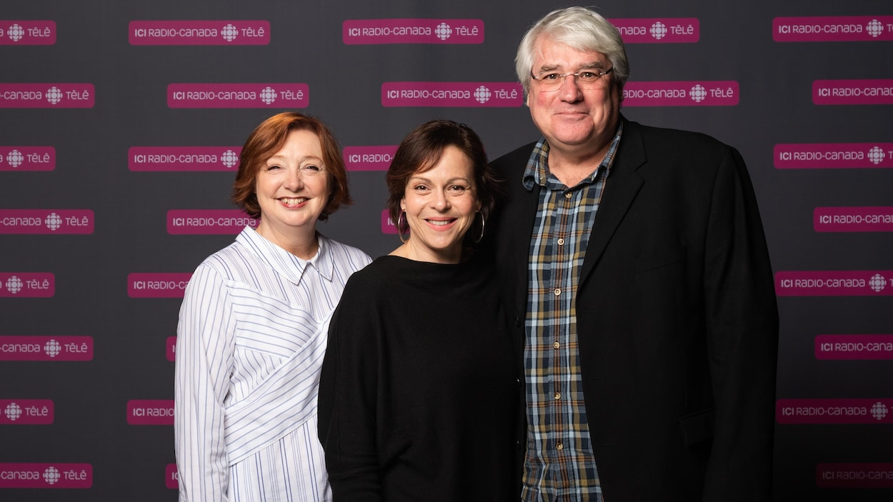 Sylvie Lussier, Maude Guérin et Pierre Poirier sourient et posent pour les photographes, devant un panneau où se trouvent plusieurs logos d'ICI Radio-Canada Télé.