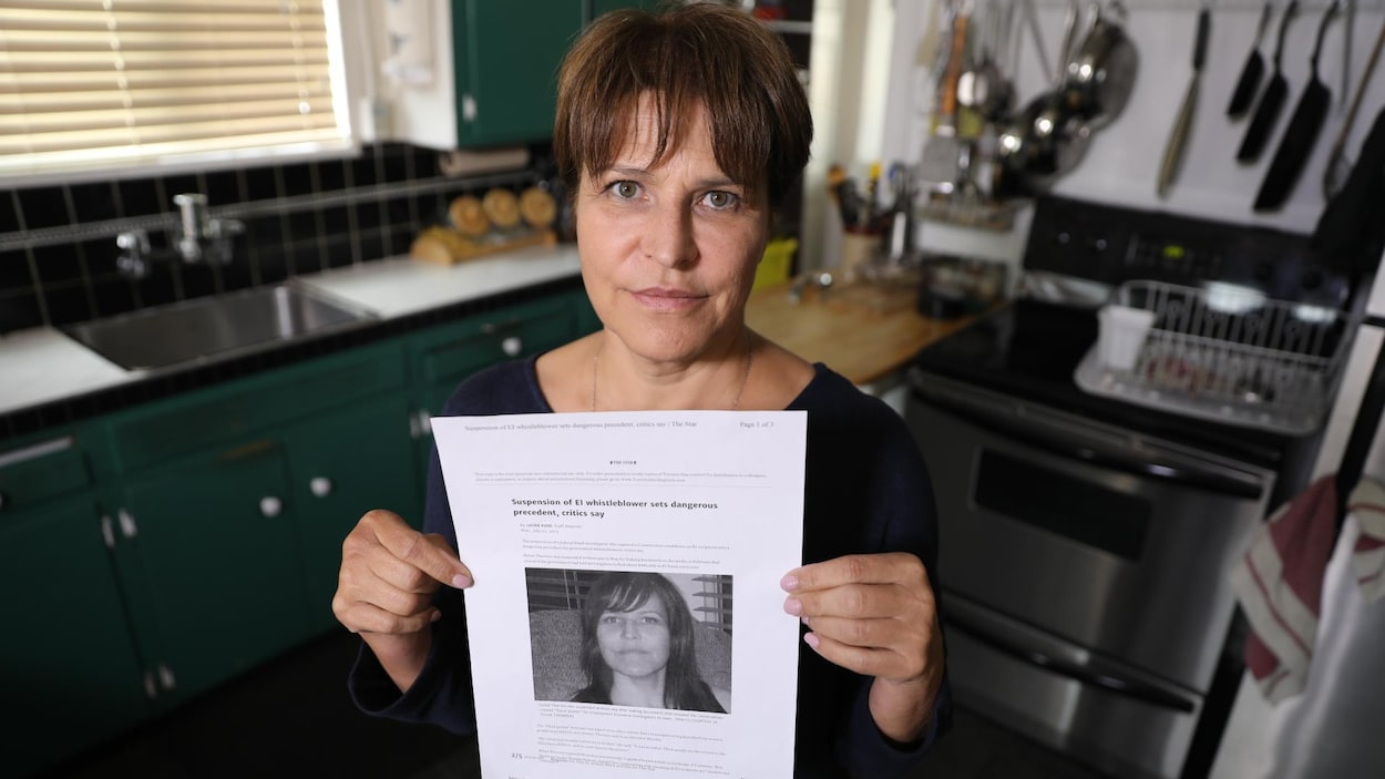 Une femme se tient debout dans une cuisine, tenant en main la version imprimée d'un article de journal.