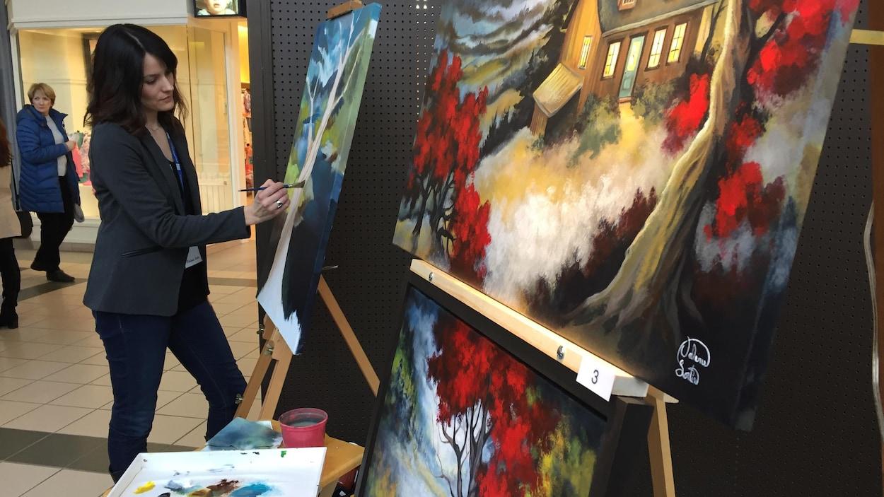 Une artiste peint dans le cadre du Symposium des arts de Drummondville