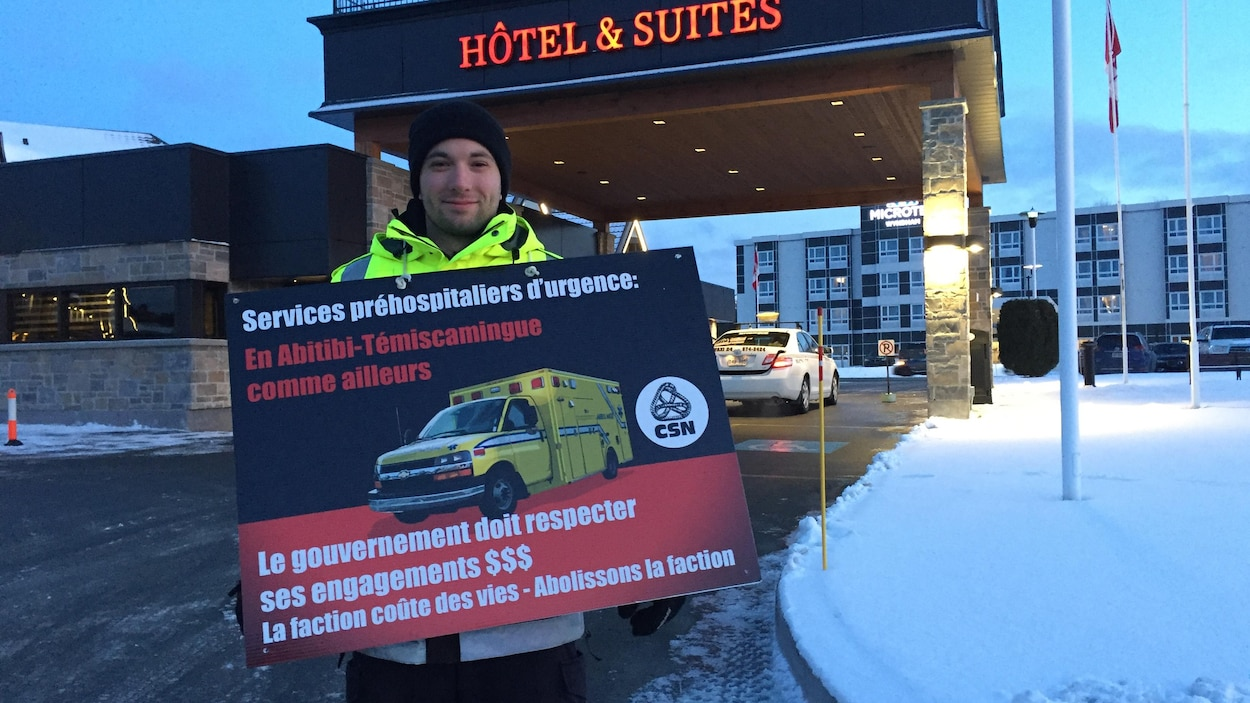 Un ambulancier tient une affiche lors d'une manifestation.