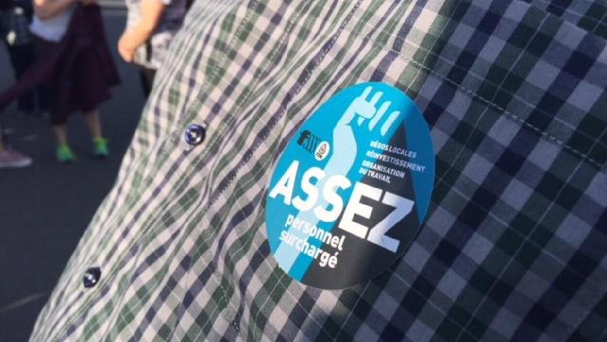 Une chemise sur laquelle est apposé un autocollant « Assez personnel surchargé ».