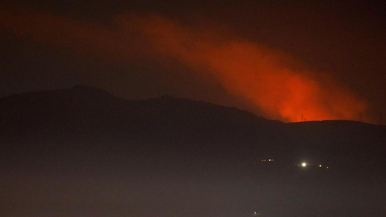 Une vue sur une colonne de fumée rougeâtre s'élevant derrière des montagnes dans la nuit près de Damas, en Syrie.