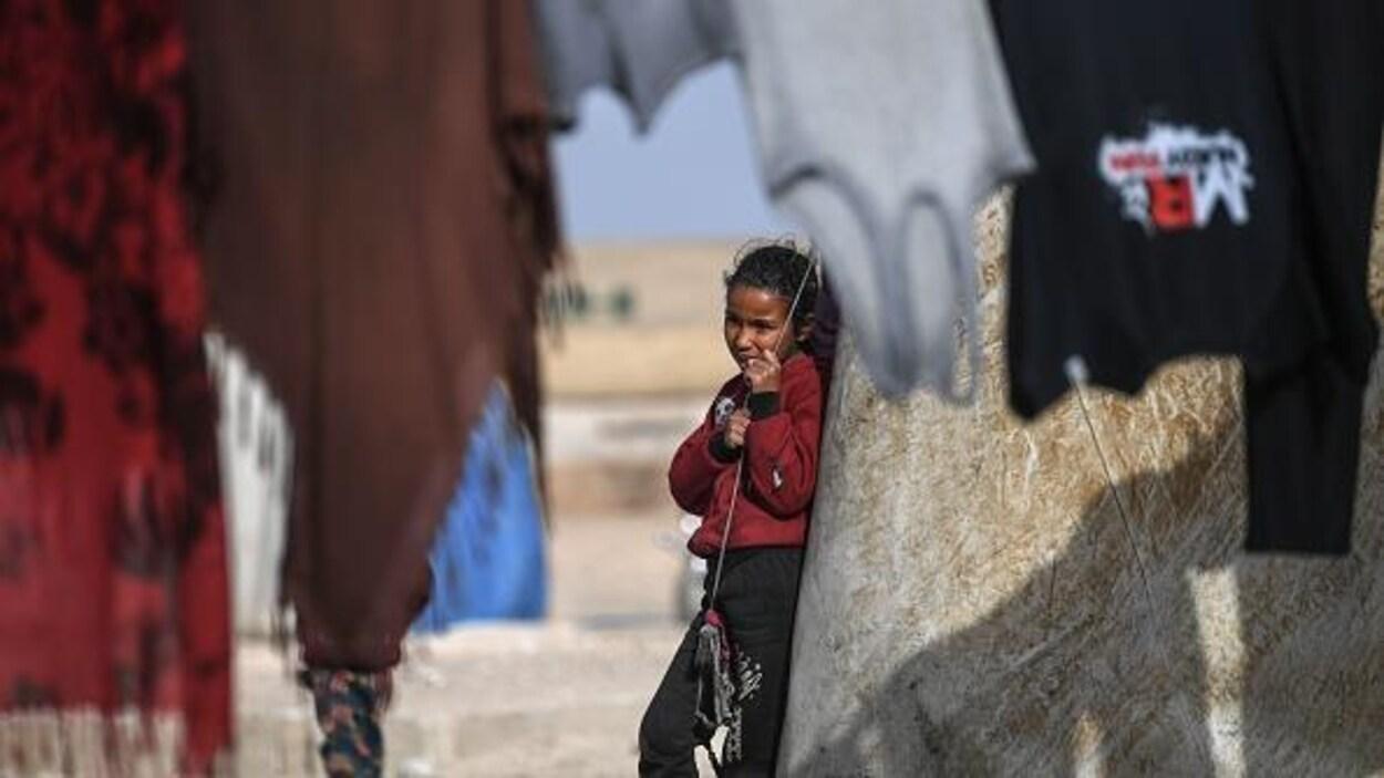 Une jeune Syrienne à l'extérieur d'une tente, dans un camp de réfugiés.