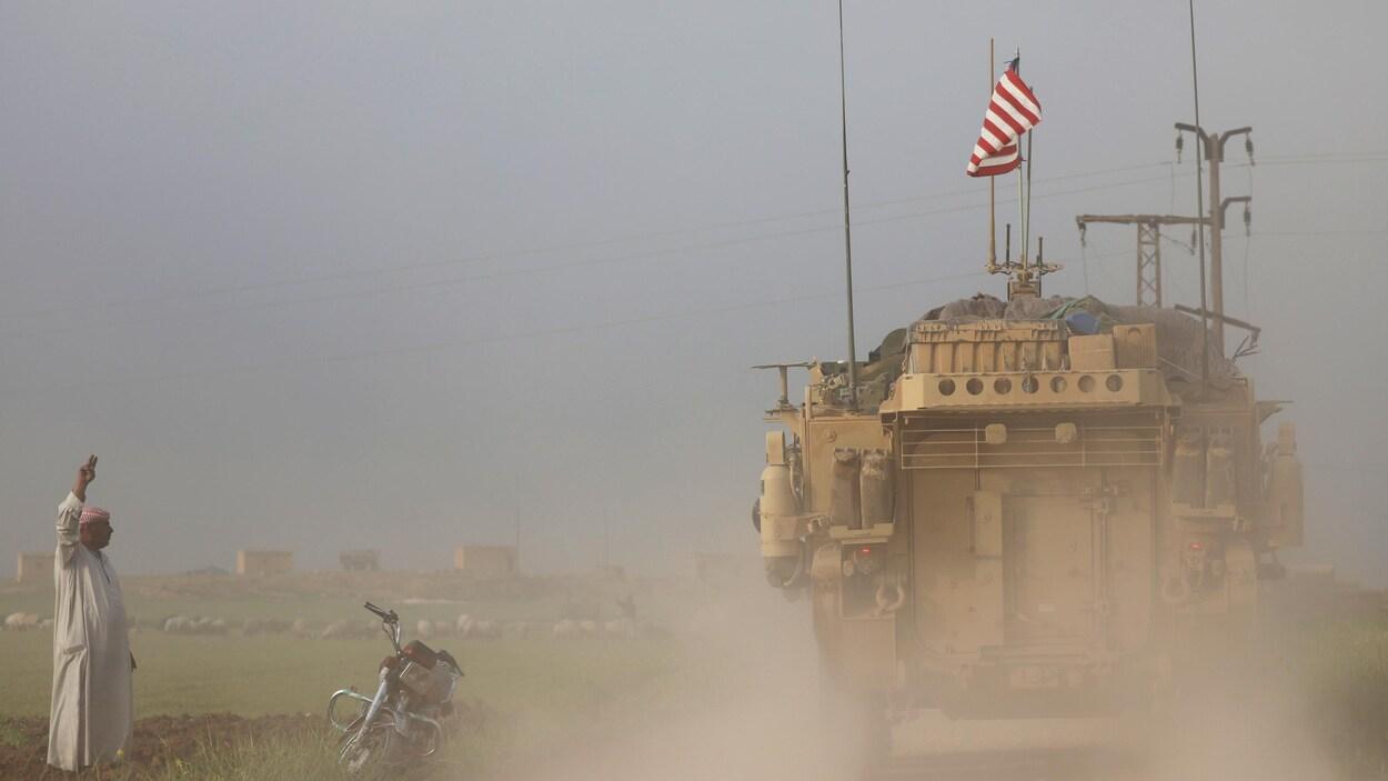 Un homme effectue un geste du bras en direction d'un véhicule blindé arborant le drapeau américain.