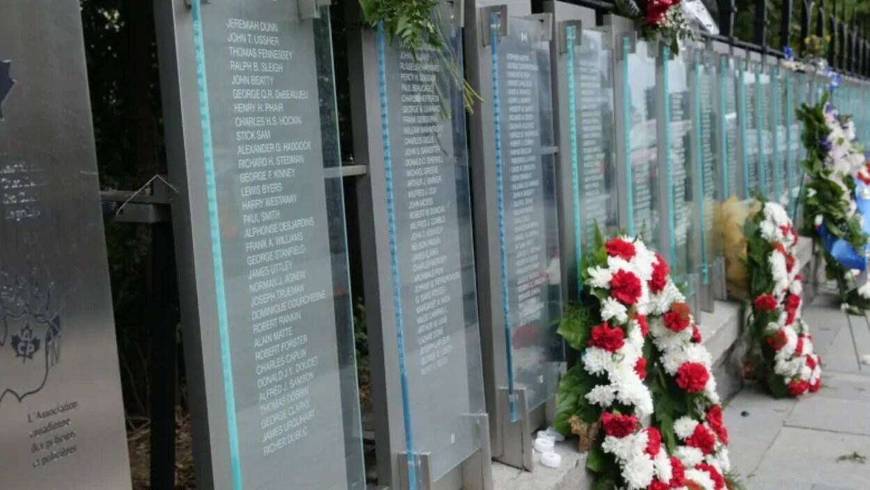 Les noms inscrits sur le Tableau d'honneur et des gerbes de fleurs.