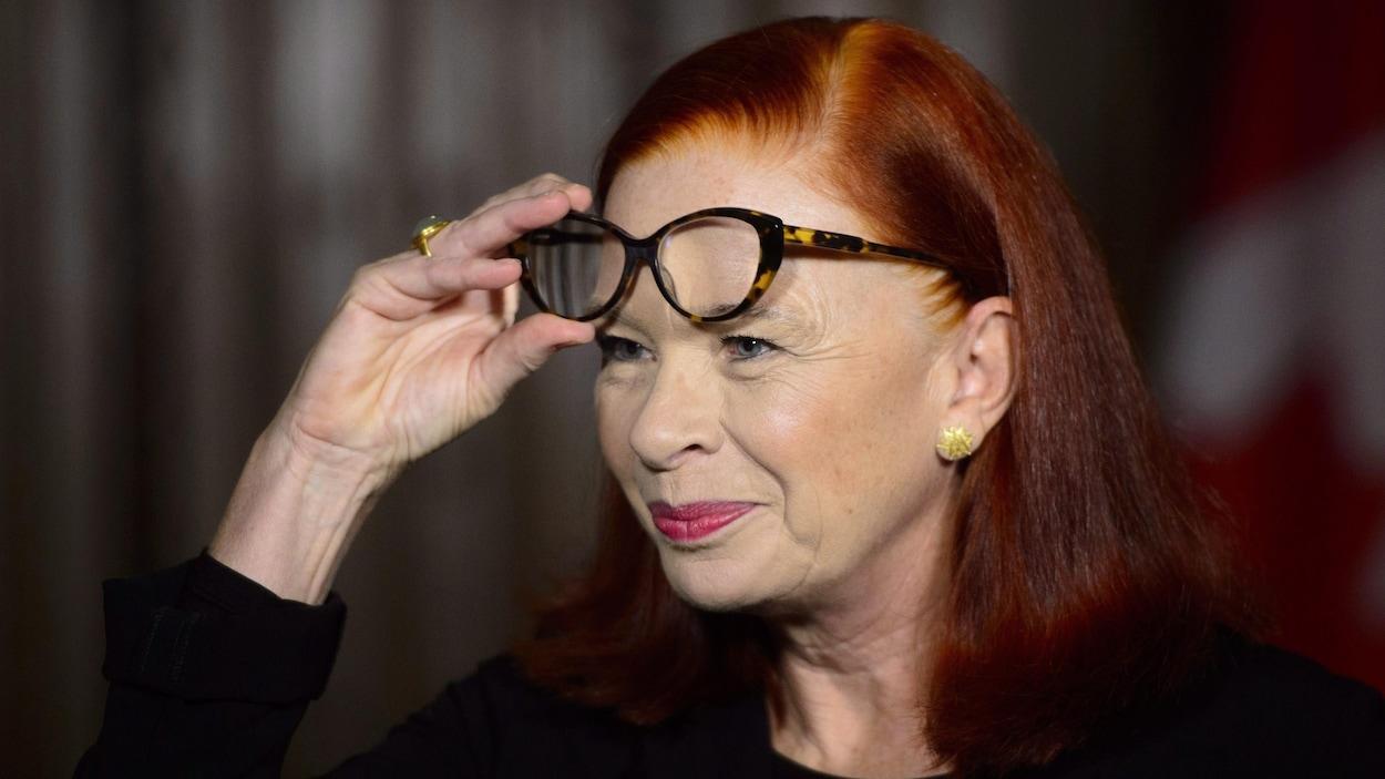 Catherine Tait soulève ses lunettes pour répondre à un journaliste.