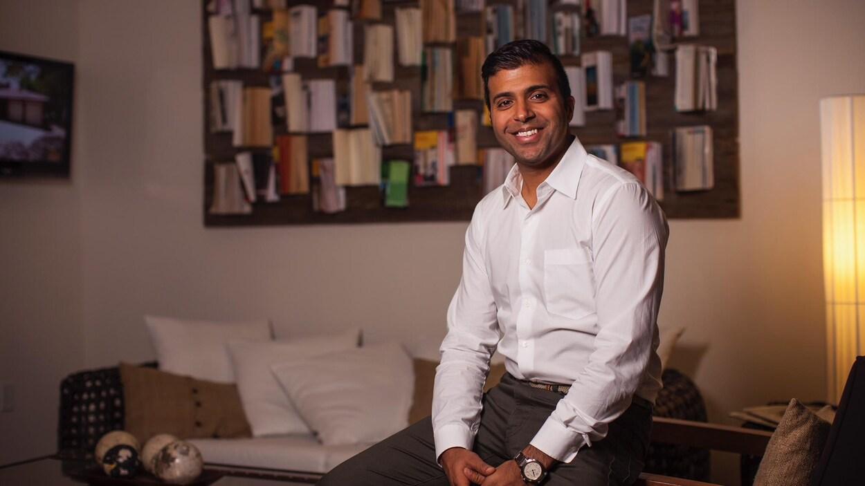 Un homme souriant pose dans un appartement.