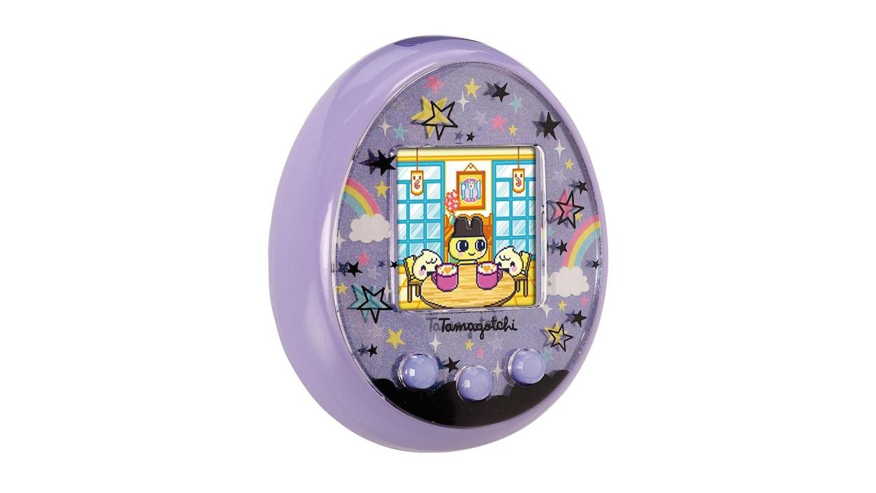 Une photo montrant un jouet Tamagotchi On. L'objet est en forme d'oeuf applati et présente un petit écran carré sur sa face avant.