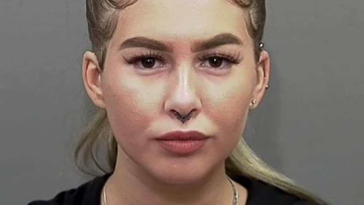 Une jeune fille maquillée, avec des boucles à une oreille et au nez, regarde directement l'objectif de la caméra.