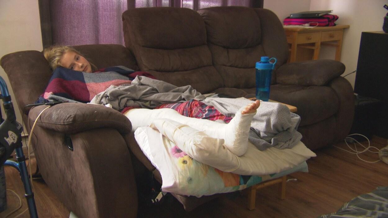Une adolescente avec la jambe recouvert d'un plâtre est couchée sur un divan.