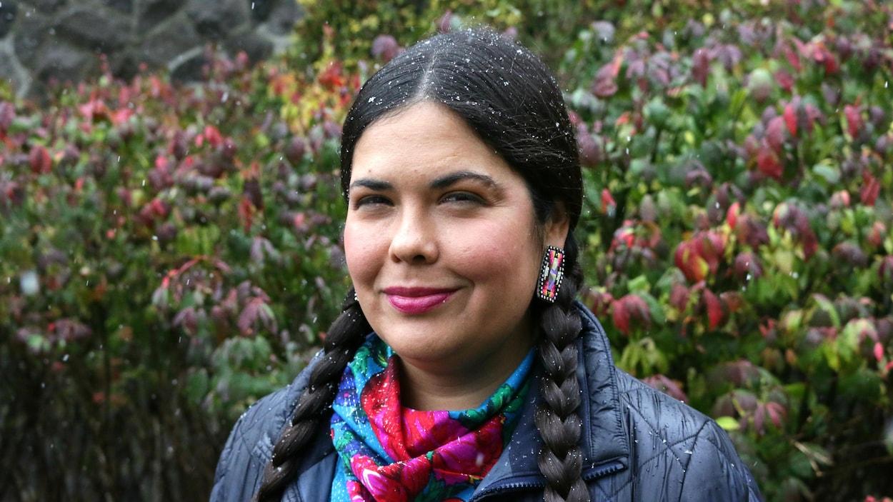 La militante autochtone Tara Houska devant un arbre pendant une légère tempête de neige.